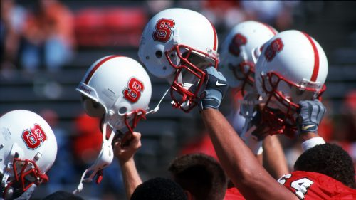 NC State football players raise their helmets in unity as they walk off the field.