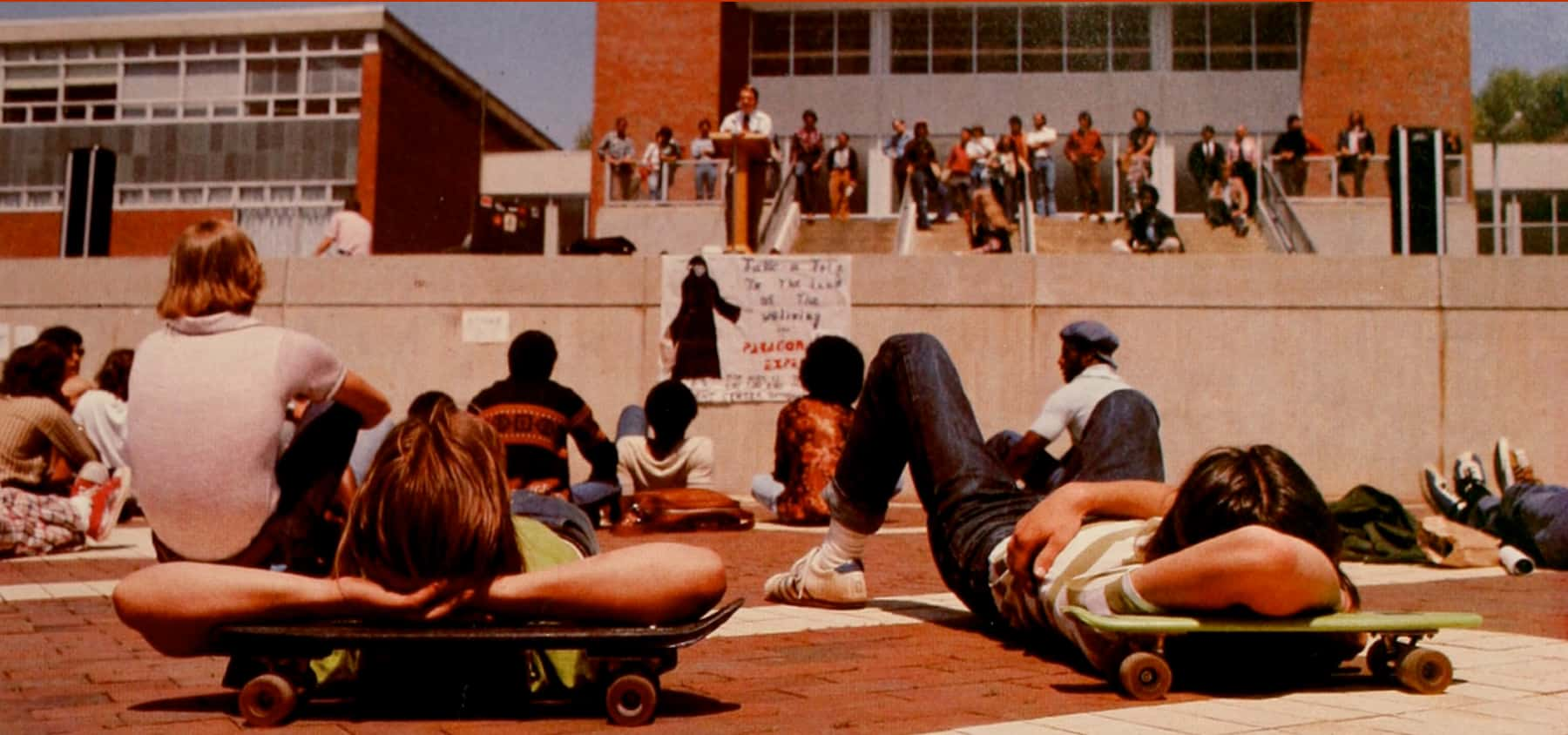 Students lie on skateboards in the brickyard while listening to a speaker