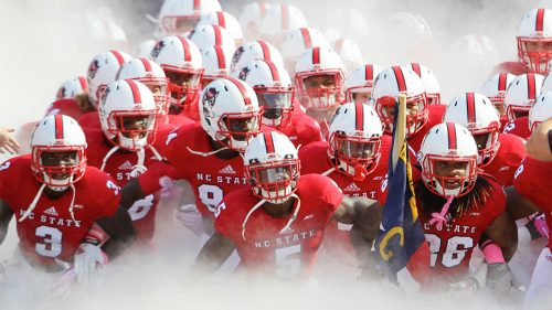 The NC State football team emerges from smoke